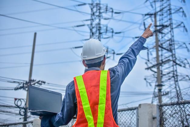 Ingeniero con computadora portátil de alto voltaje de la planta de energía