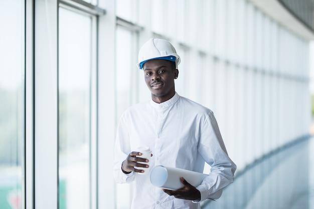 Ingeniero de construcción afroamericano en frente del edificio con planos contra ventanas
