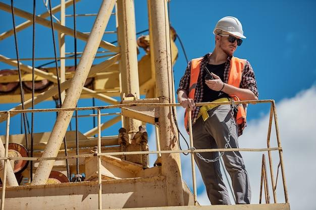 Un ingeniero de construcción con una camisa a cuadros, chaleco naranja y casco blanco en una grúa de construcción amarilla con un walkie-talkie en sus manos. capataz, supervisor, trabajador