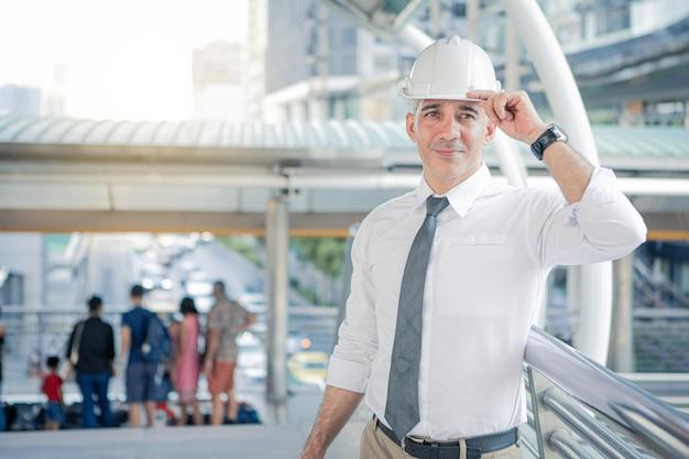 Ingeniero de construcción confía en casco mirando proyectos de construcción.