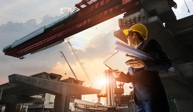 Ingeniero de construcción encargado de supervisar el progreso de la estación de bts y la tableta con plano en las manos.