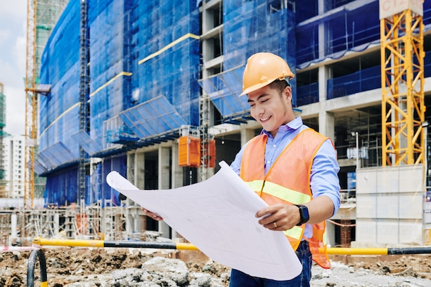Ingeniero de construcción examinando planos de construcción