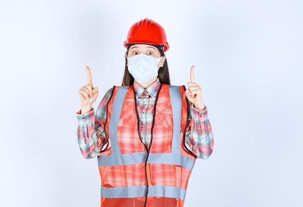 Ingeniero de construcción femenino en casco rojo y máscara de seguridad apuntando hacia arriba.