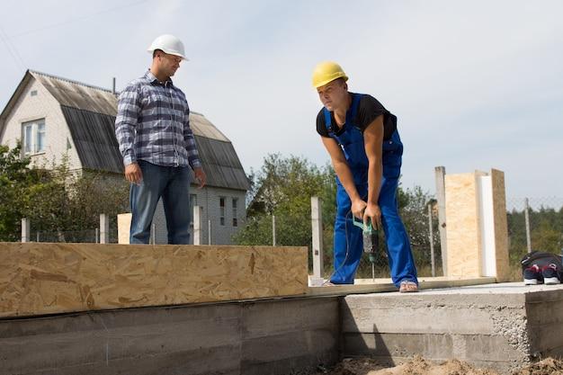 Ingeniero de construcción masculino mirando trabajador de la construcción ocupado perforando una madera en el sitio.