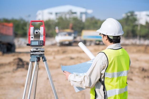 Ingeniero de construcción que controla el dibujo de construcción en el área del sitio