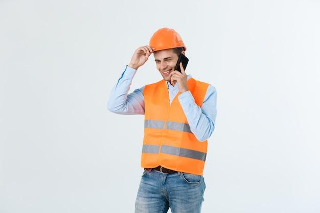 Ingeniero de construcción sonriente posando aislado sobre fondo gris.
