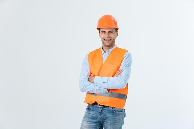 Ingeniero de construcción sonriente posando con los brazos cruzados. aislado sobre fondo gris.