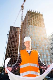 Ingeniero de la construcción de vista de ángulo bajo de tiro medio mirando planes