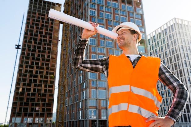 Ingeniero de construcción de vista lateral de plano medio mirando a través de planos