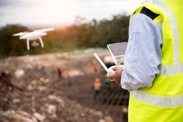 Ingeniero de construcción volar un avión no tripulado para tomar una foto para informe de progreso