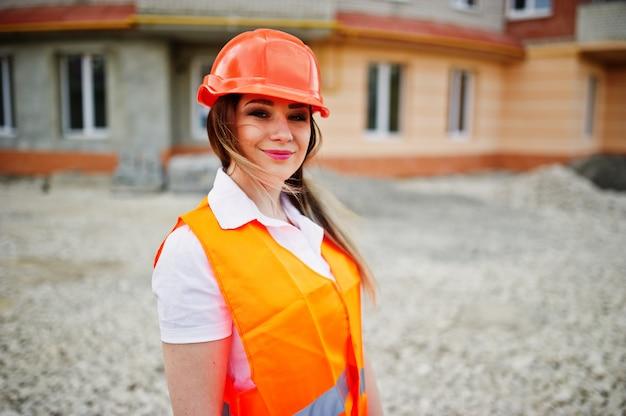 Ingeniero constructor mujer en uniforme chaleco y casco protector naranja contra nuevo edificio
