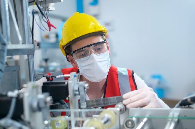 Ingeniero de control de calidad (qc) que supervisa y verifica el sistema de la máquina en la fábrica de fabricación