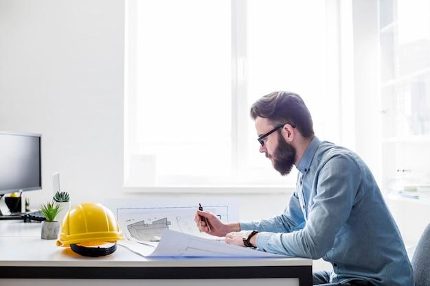Ingeniero creativo trabajando en planos de construcción en el lugar de trabajo