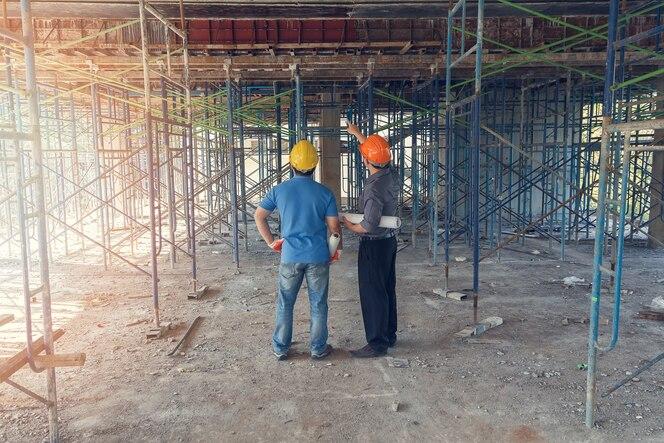 Ingeniero discutiendo con el capataz sobre el proyecto en el sitio de construcción
