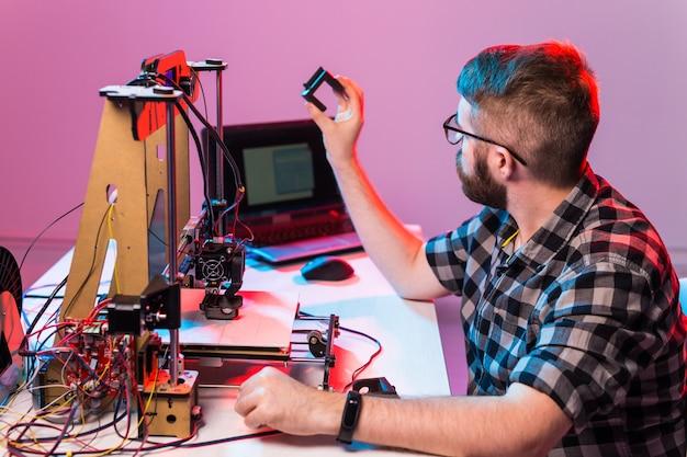 Ingeniero diseñador masculino joven que usa una impresora en el laboratorio y estudia un concepto de prototipo, tecnología e innovación de producto.