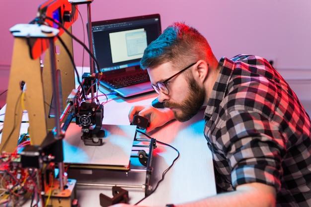 Ingeniero diseñador masculino joven que usa una impresora en el laboratorio y estudia un prototipo de producto