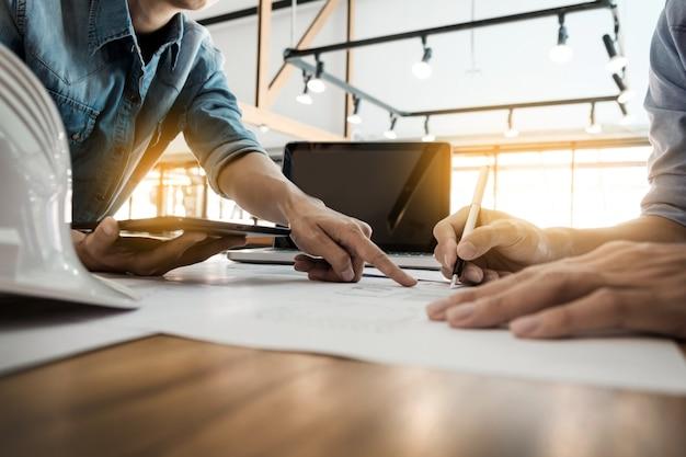 Ingeniero de dos arquitectos discutir los datos de trabajo y tableta, portátil con el proyecto - closeup en manos y proyecto de impresión