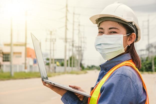 Ingeniero de electricidad de las mujeres que trabajan en el servicio del sitio con la computadora
