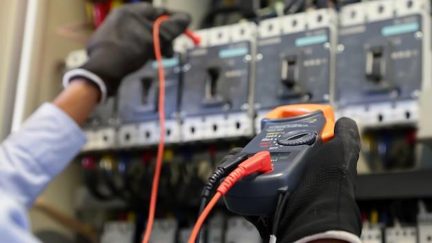 Ingeniero eléctrico con multímetro digital para verificar el voltaje de la corriente eléctrica en el disyuntor.