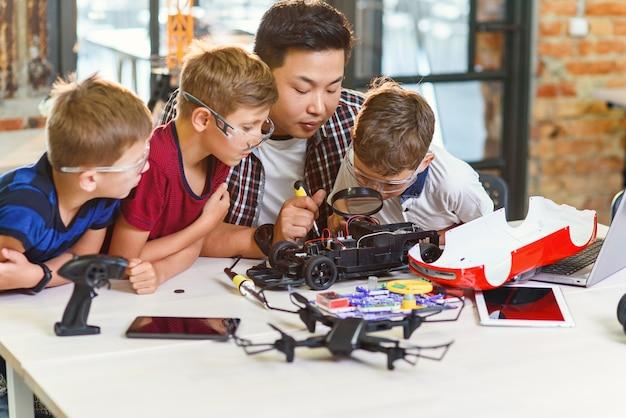 Ingeniero electrónico con escolares europeos que trabajan en el laboratorio de la escuela moderna y prueban un modelo de automóvil eléctrico