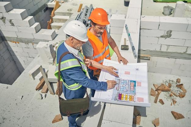Ingeniero enfocado y un constructor en cascos protectores examinando un dibujo