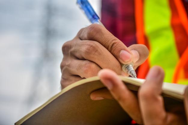 Ingeniero escribiendo en el cuaderno en el trabajo