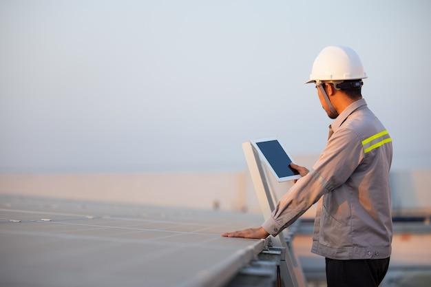 Ingeniero de la estación de paneles fotovoltaicos solares verificaciones con tableta. concepto de tecnología energética
