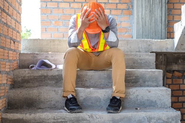 Ingeniero de estrés o arquitecto tomados de la mano a la cabeza. está teniendo problemas en el trabajo. el esta sentado en las escaleras. concepto de ingeniería.
