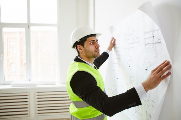 Ingeniero estudiando planes en el sitio