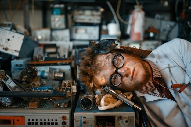 Ingeniero extraño durmiendo en dispositivos en laboratorio. equipo de laboratorio, taller de ingeniería