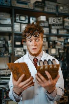 Ingeniero extraño mira chips electrónicos en laboratorio. equipo de laboratorio, taller de ingeniería