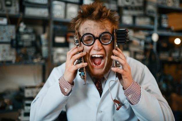 Un ingeniero extraño tiene chips electrónicos en su cara en el laboratorio. equipo de laboratorio, taller de ingeniería