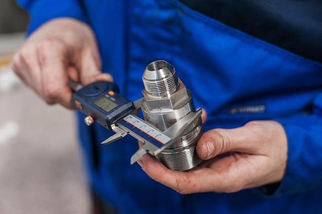 Ingeniero en fábrica con aprendiz comprueba la calidad de los componentes