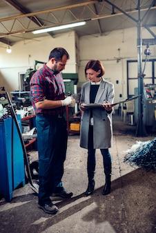 Ingeniero femenino que consulta con un maquinista que mide el diámetro del eje del engranaje
