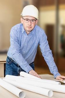 Un ingeniero con gafas y un casco de construcción se inclinó sobre la mesa con los documentos. realizar cambios en los planos de construcción. imagen vertical.