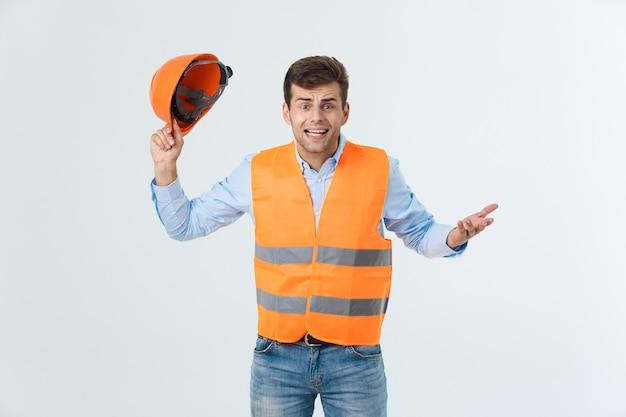 Ingeniero guapo decepcionado con chaleco naranja y jeans con casco, aislado sobre fondo blanco.