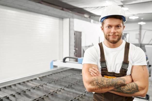Ingeniero guapo posando en fábrica cerca de cortador de plasma.