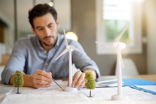 Ingeniero hermoso de la turbina de viento que trabaja en oficina moderna