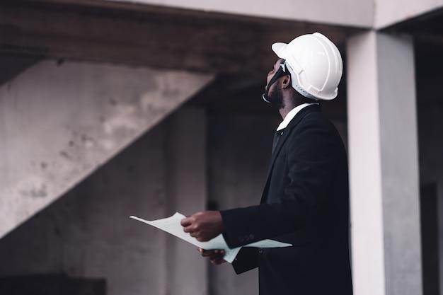 Ingeniero hombre africano mirando el edificio inacabado