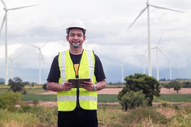Ingeniero hombre asiático con tableta portátil con turbina eólica