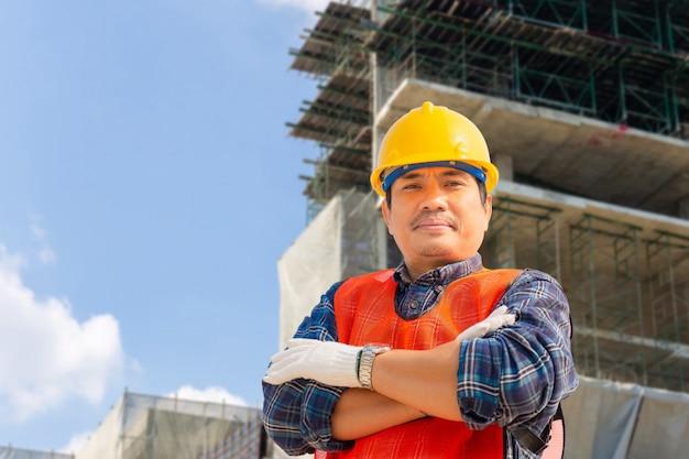 Ingeniero hombre / trabajador con trazado de recorte comprobación y planificación del proyecto en el sitio de construcción, hombre sonriente sobre fondo borroso