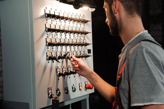 El ingeniero de iluminación ajusta las luces en el escenario cerca de las escenas.