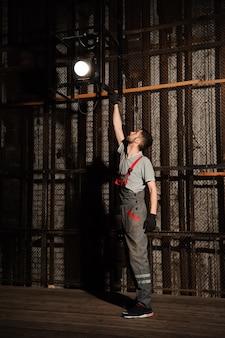 El ingeniero de iluminación ajusta las luces en el escenario.