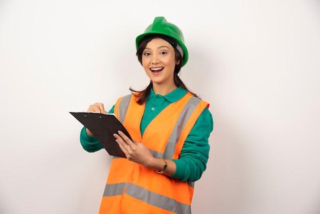 Ingeniero industrial femenino positivo en uniforme con portapapeles sobre fondo blanco.