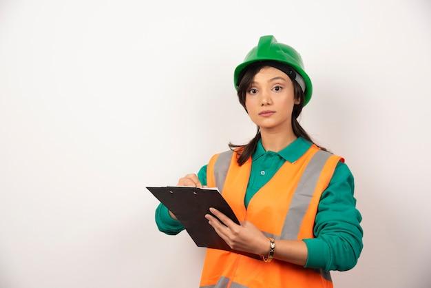 Ingeniero industrial femenino en uniforme con portapapeles sobre fondo blanco.