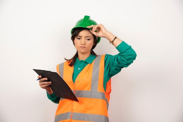 Ingeniero industrial mujer molesto en uniforme con portapapeles sobre fondo blanco.
