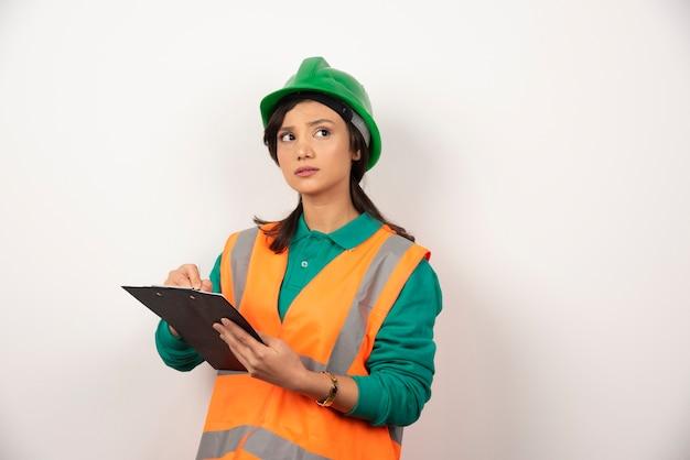 Ingeniero industrial mujer pensativo en uniforme con portapapeles sobre fondo blanco.