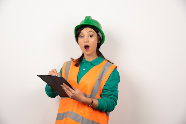 Ingeniero industrial mujer sorprendido en uniforme con portapapeles sobre fondo blanco.