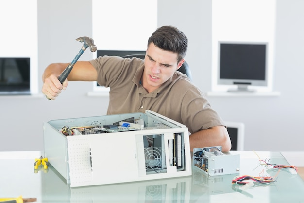 Ingeniero informático enojado atractivo que destruye la computadora con el martillo