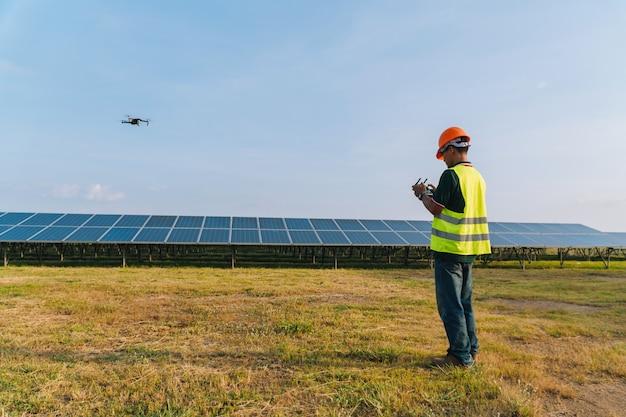 El ingeniero inspecciona y revisa el panel solar de drone en la planta de energía solar